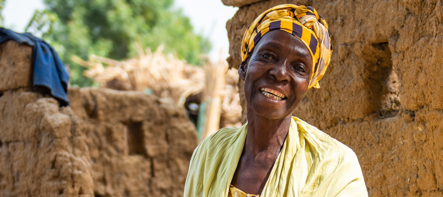 A lady from Nigeria dressed in all yellow smiles at the camera