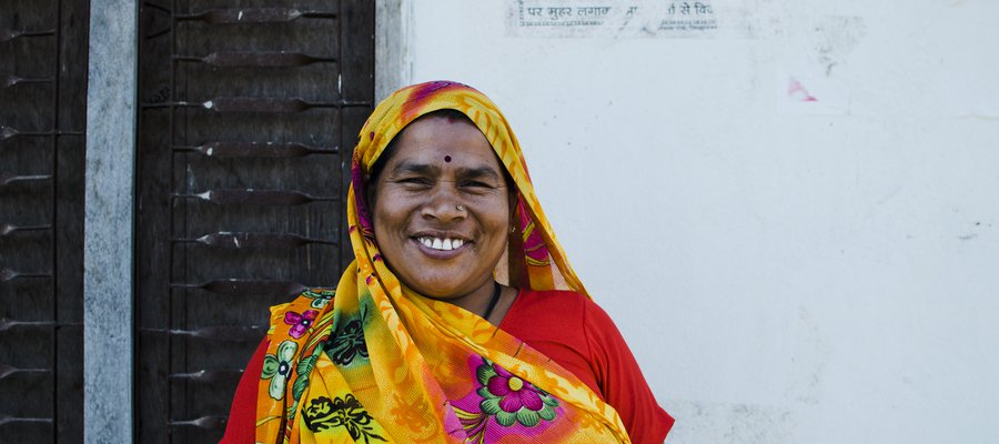 A woman in a colourful headscarf smiles at the camera