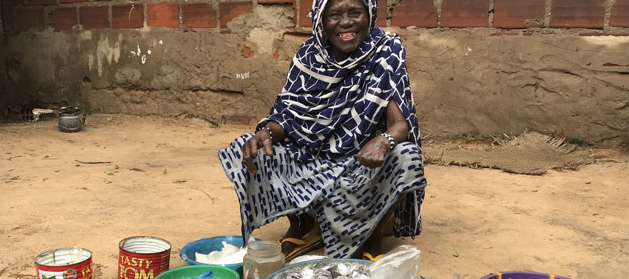 Hawa sits outside her home with the goods she is selling
