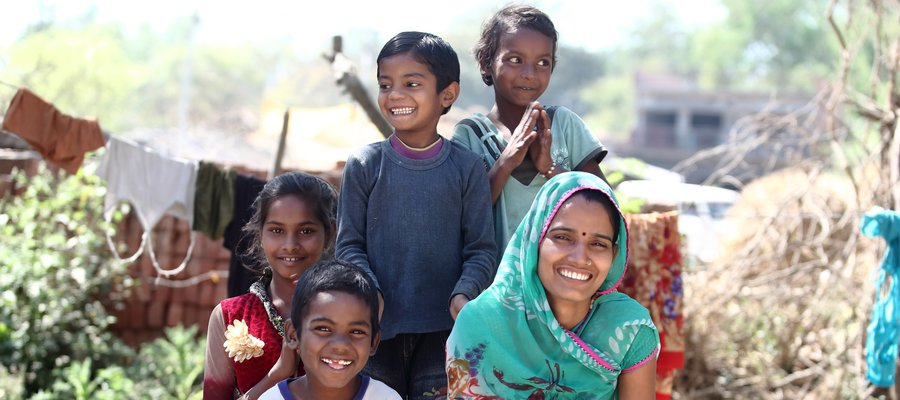 Parma (pictured here with smiling children) is a volunteer with TLM Trust India.