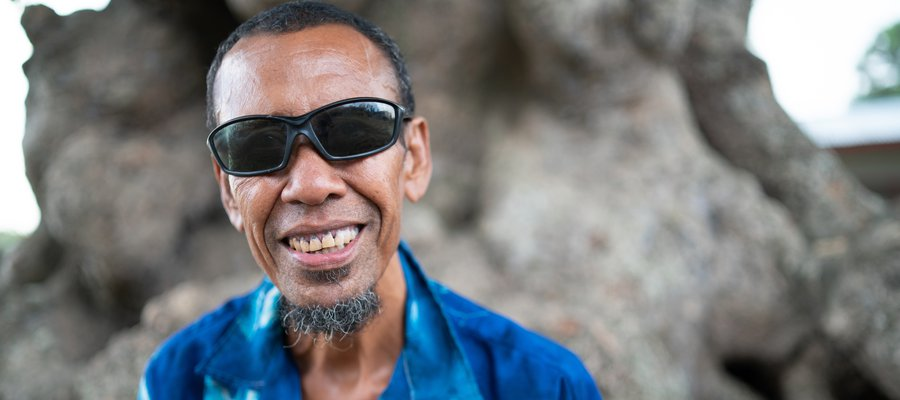 A man from Papua New Guinea wearing a blue shirt and sunglasses smiles at the camera