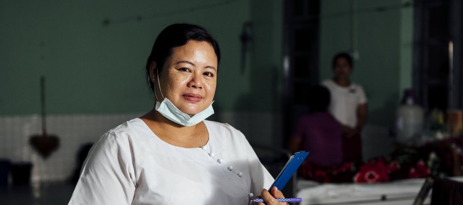 A nurse dressed in white blouse and red skirt lowers her face mask to pose for a picture at our partner hospital in Myanmar