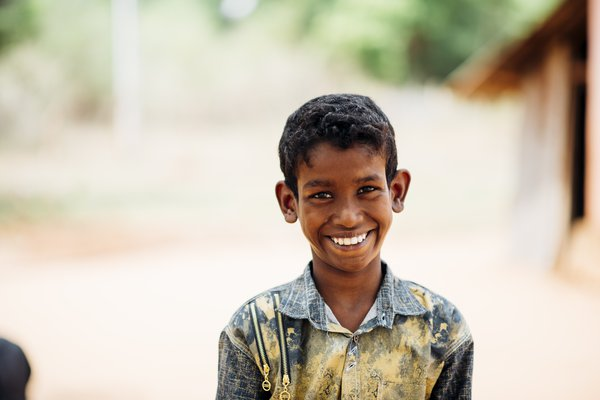 A young man affected by leprosy in Sri Lanka smiles at the camera