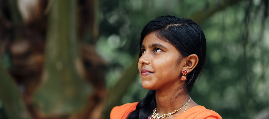 A young woman in Sri Lanka stands proudly