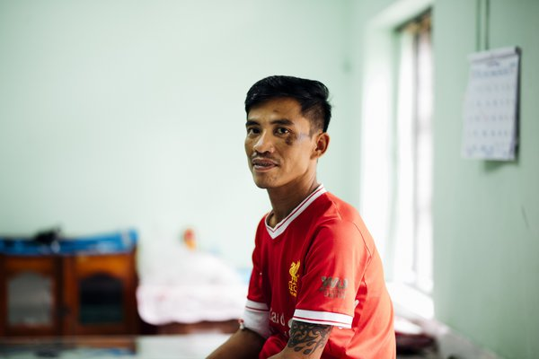 A man on a hospital bed in Myanmar looks to his left, at the photographer. He is proudly wearing a Liverpool FC top.