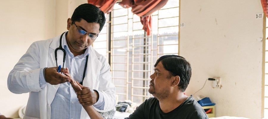 Dr Benjamin examines a patient at DBLM Hospital in Bangladesh