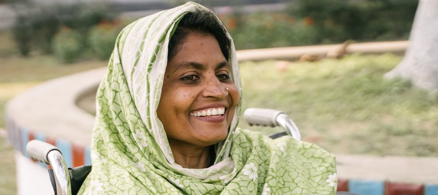 A woman sat in a wheelchair smiling at the camera. Her head is covered with a shawl.