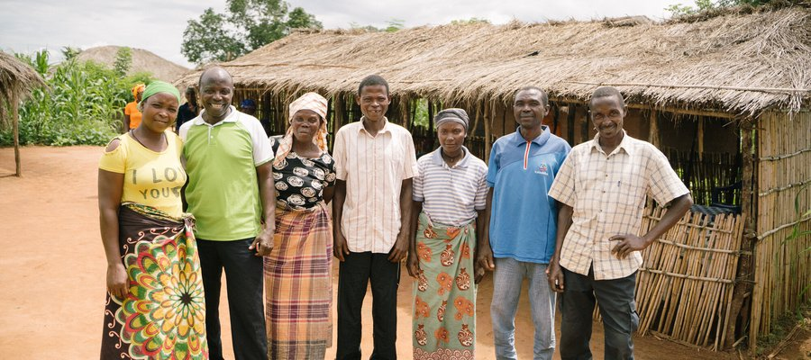 A group of people stand together, smiling in a village in Mozambique