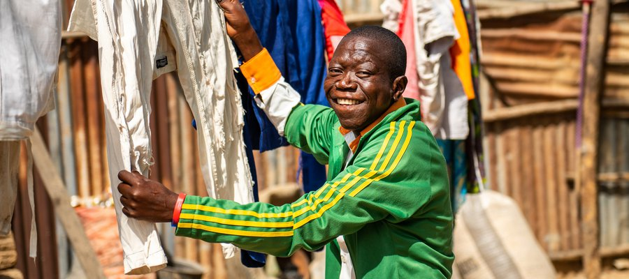A man smiles at the camera while hanging up clothes to dry