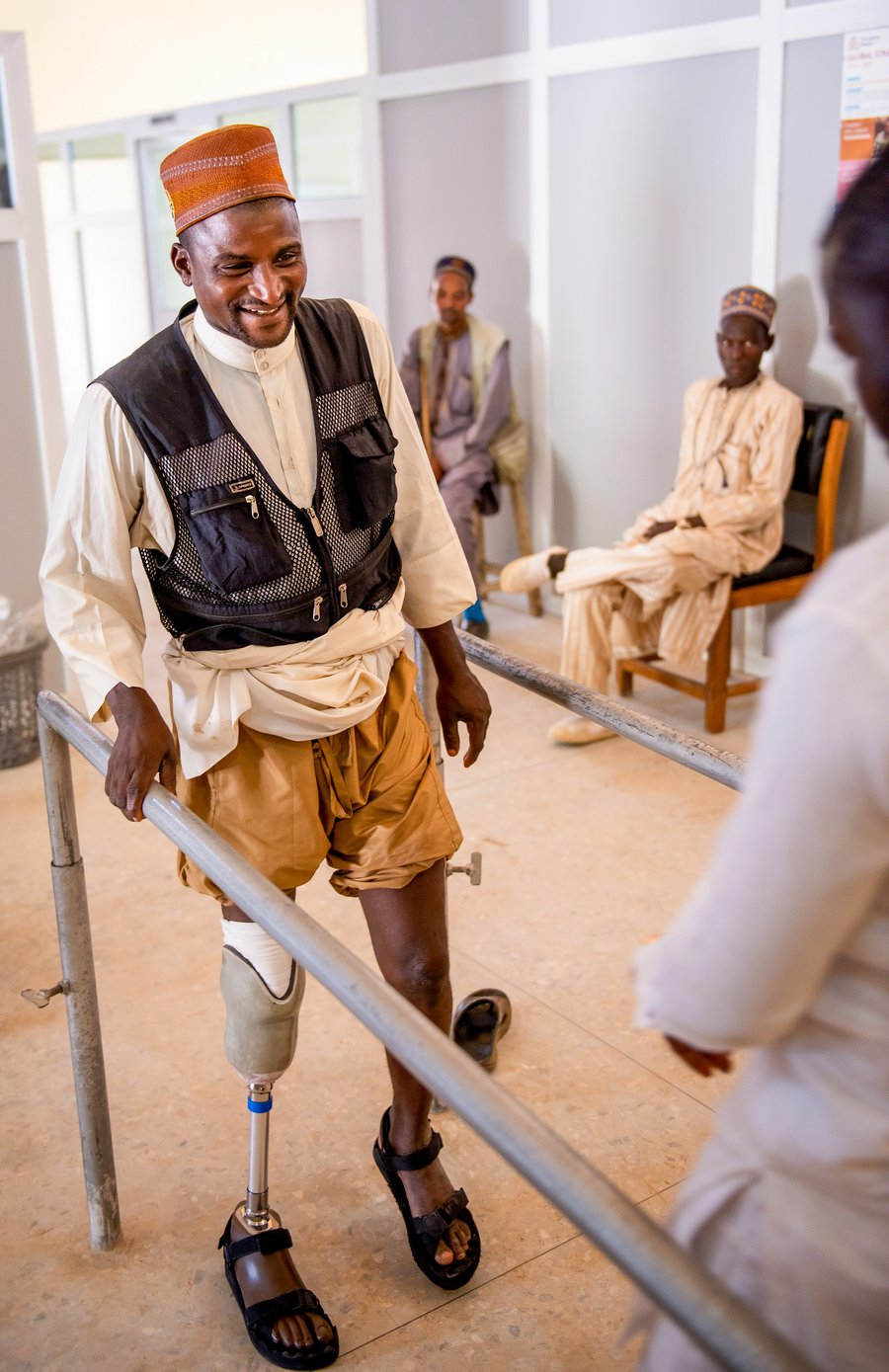 Nuhu holds onto handrails at TLM's workshop as he practices using his new prosthetic leg