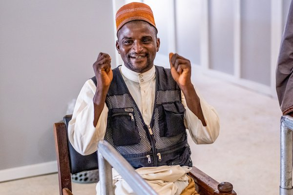 Nuhu sits in a chair, smiling and holding his fists up in celebration at completing a walk with his new prosthetic leg