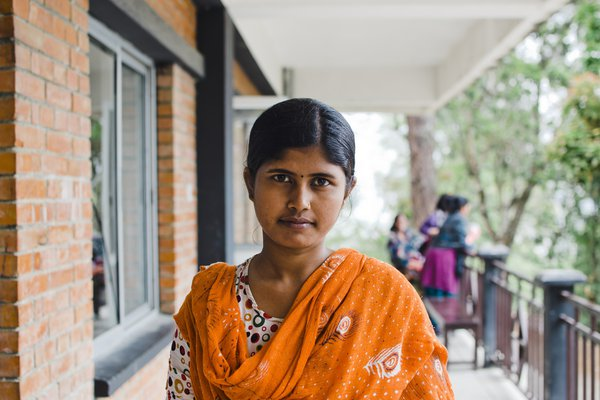 A woman in an orange sari looks at the camera