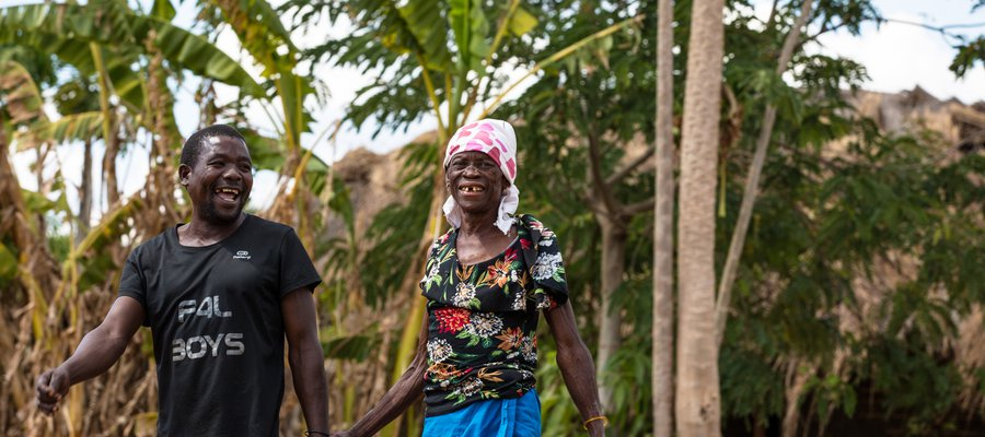 Two people hold hands in a village in Mozambique