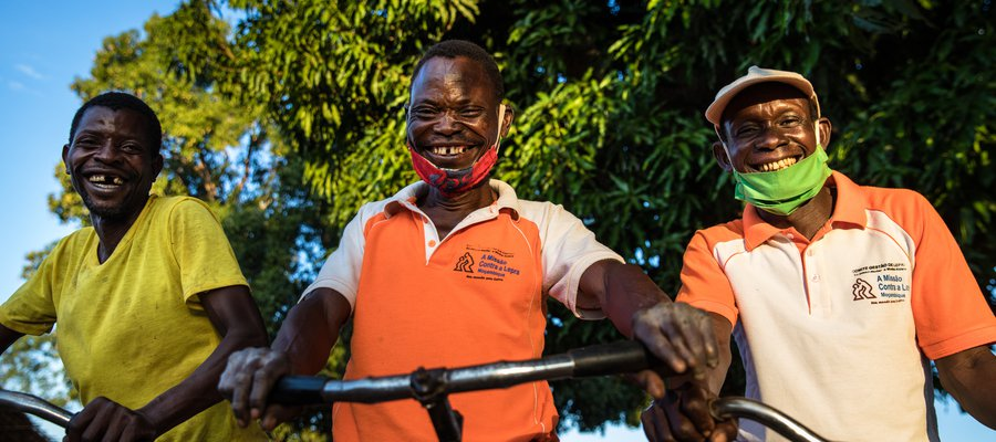 Three men in Mozambique stand with their bikes, smiling