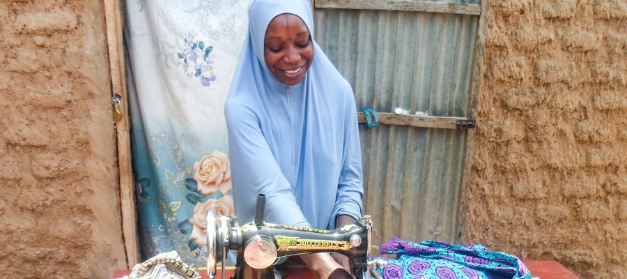 Mariama has received job training and is a skilled seamstress making clothes to sell