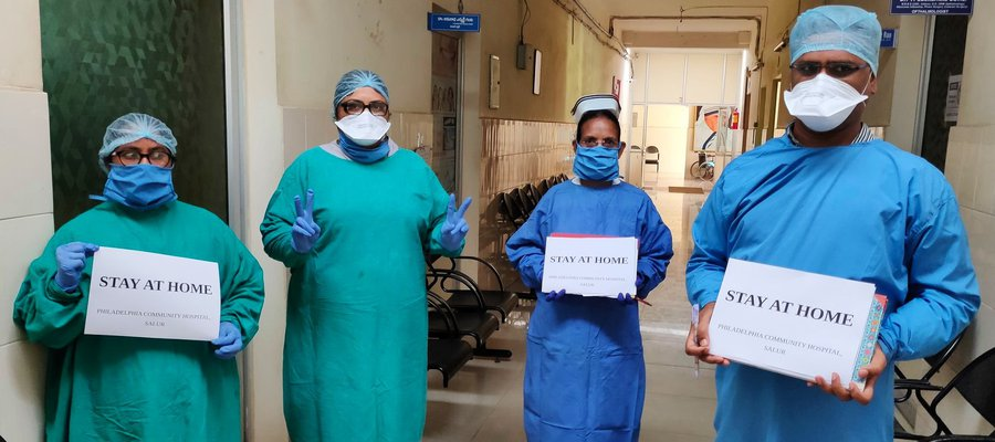 Doctors in PPE hold up 'Stay at home' signs