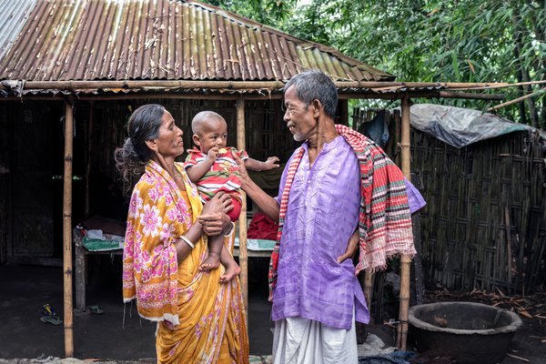 A grandmother in a village in Bangladesh holds her grandson while her husband talks to him