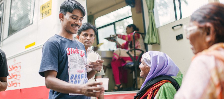 Karuna Mobile Clinic - people share cups of chai together at the clinic