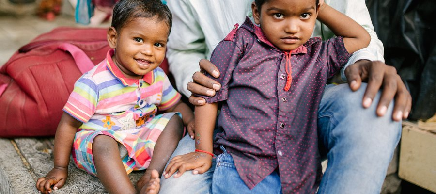 Two young children sit with their father in India