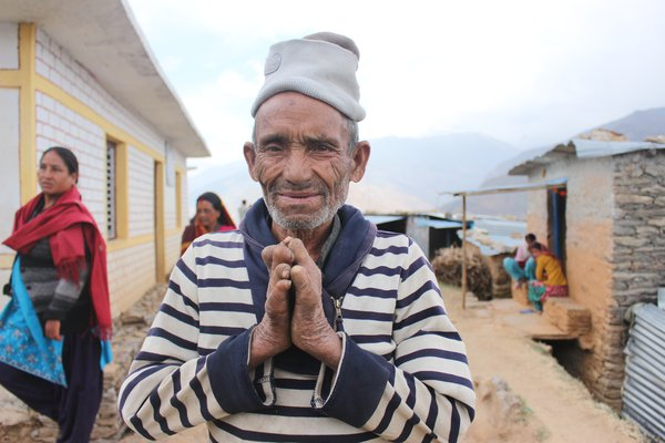 A man in Nepal looks to camera and holds his leprosy-affected hands together in front of him