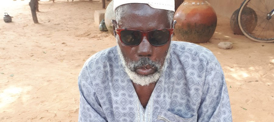 A man affected by leprosy in Niger sits on a mat, wearing sunglasses. He lost his site due to leprosy.
