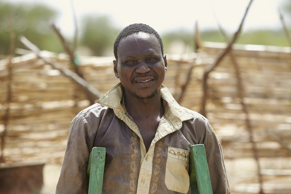 Lau, a person affected by leprosy, stands on his crutches looking at the camera
